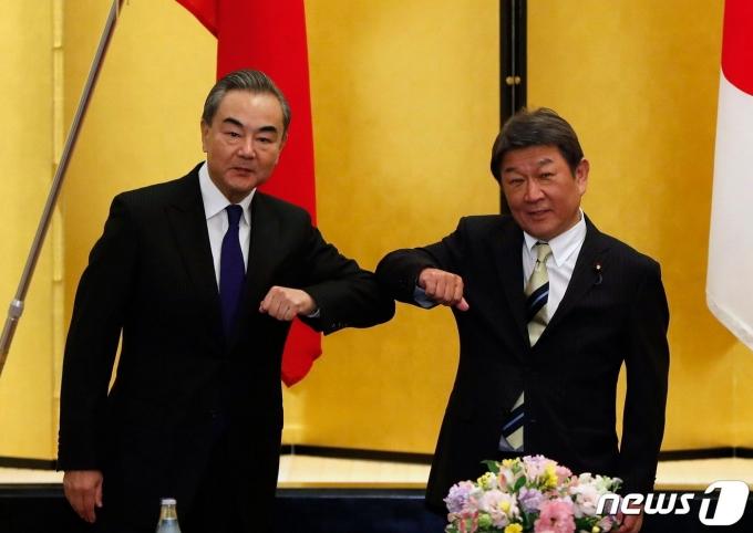 왕이 중국 외교부장(사진 왼쪽)과 모테기 도시미쓰 일본 외무상. © AFP=뉴스1