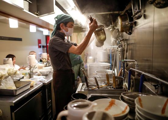 20일 일본 도쿄의 한 라면집에서 16세 요리사 하가 야시로가 방역을 위해 마스크를 착용한 채 요리를 하고 있다. /사진=로이터
