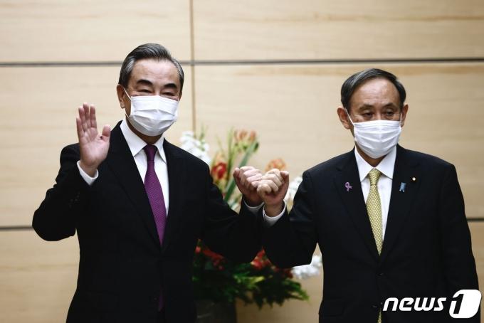 왕이 중국 국무위원 겸 외교부장(왼쪽)과 스가 요시히데 일본 총리 © AFP=뉴스1