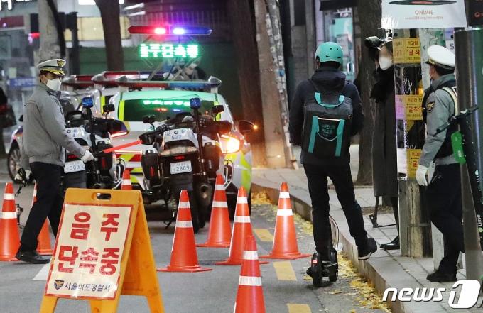 27일 저녁 서울 마포구 서교동 일대에서 경찰들이 음주 단속을 실시하고 있는 가운데 전동킥보드로 차도를 달리던 배달원이 단속 구간을 그냥 지나치기 위해 인도(오른쪽)로 올라가려다 경찰에 제지당하고 있다. 해당 배달원은 음주상태는 아닌것으로 전해졌다. 서울경찰청은 연말연시를 맞아 지난 24일부터 내년 1월 23일까지 2개월간 음주운전 특별 단속을 실시한다. 특히 최근 이용자가 많이 늘어난 전동킥보드와 자전거 운전자를 대상으로 한 음주단속도 강화될 예정이다. 2020.11.27/뉴스1 © News1 이성철 기자