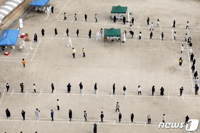 학교 운동장에 설치된 이동식 선별진료소에서 코로나19 진단검사를 받기 위해 기다리는 학생들./뉴스1 © News1 장수영 기자