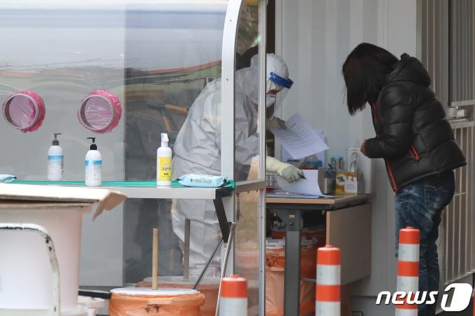 보건소 관계자들이 코로나19 검사를 위해 찾아온 시민들의 검체를 채취하고 있다./뉴스1 © News1 공정식 기자