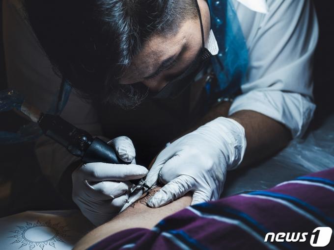 타투이스트 이유철씨가 고객의 몸에 문신을 새겨 넣고 있다. (노마드 스튜디오 제공)© 뉴스1