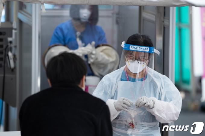 코로나19 일일 확진자가 0시 기준 686명 발생한 9일 서울 중구 국립중앙의료원 선별진료소에서 의료진이 채취한 검체를 옮기고 있다. /사진=뉴스1