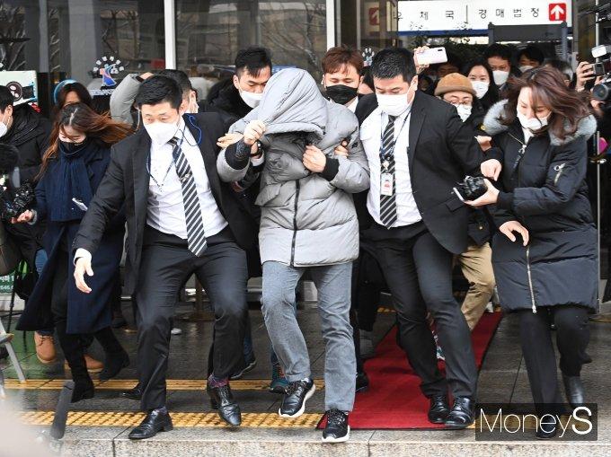 이른바 '정인이 사건' 가해자로 재판에 넘겨진 양부 안모씨(가운데 회색점퍼)가 13일 서울남부지법에서 열린 첫 공판에 출석했다. 사진은 안모씨가 공판을 마친뒤 법원을 빠져나가는 모습. /사진=장동규 기자