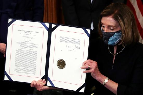 미국 하원의장인 낸시 펠로시가 13일(현지시간) 가결된 도널드 트럼프 대통령의 탄핵소추안을 들어보이고 있다. /사진=로이터