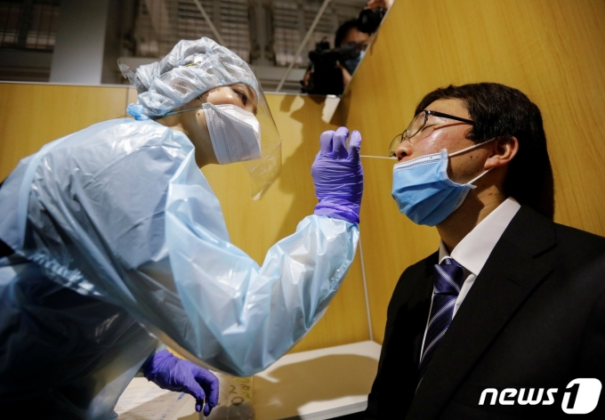 일본 도쿄도 나리타 국제공항의 한 선별진료소에서 의료진이 코로나19 진단검사를 실시하고 있다. © 로이터=뉴스1