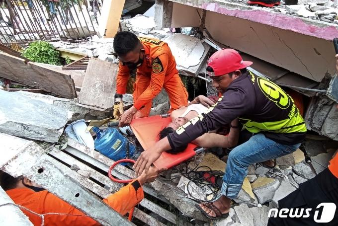 규모 6.2 강진이 발생한 인도네시아 웨스트술라웨시 마무주에서 구조대원들이 건물 잔해에 깔린 생존자를 구조하고 있다. © 로이터=뉴스1