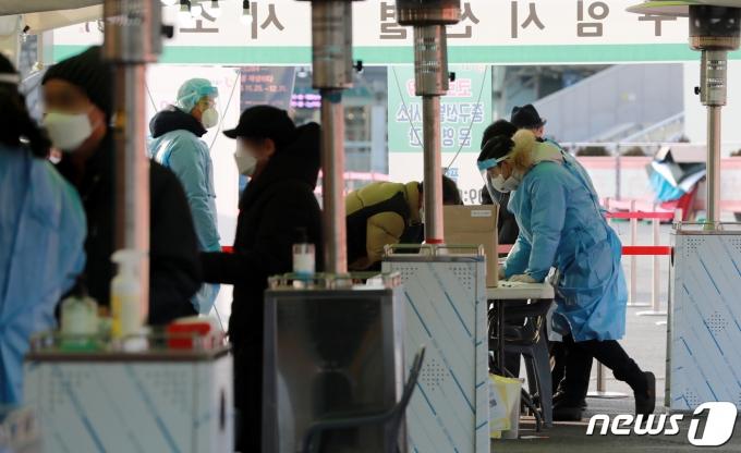14일 오전 서울역 광장에 마련된 신종 코로나바이러스 감염증(코로나19) 임시선별진료소에서 의료진이 피검사자의 검체를 채취하고 있다./사진=뉴스1