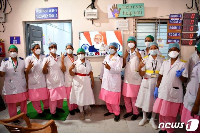 16일 접종작전 개시를 알리는 나렌드라 모디 인도 총리 연설 TV 화면 앞에서 뭄바이 소재 라자와디병원 간호사들이 승리의 V자를 만들어보이고 있다.  © AFP=뉴스1