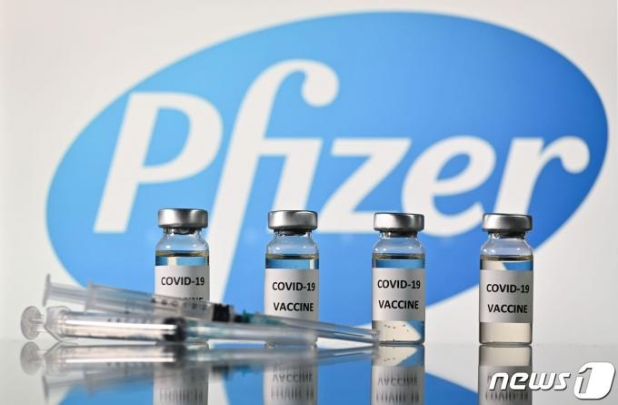 코로나19 백신 스티커가 부착된 병과 미국 제약회사 화이저 로고가 부착된 주사기. © AFP=뉴스1