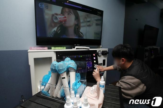17일 오후 경기 광명시의 한 코인노래방에서 점주가 영업 재개를 위해 매장을 점검하고 있는 모습. 2021.1.17/뉴스1 © News1 김진환 기자