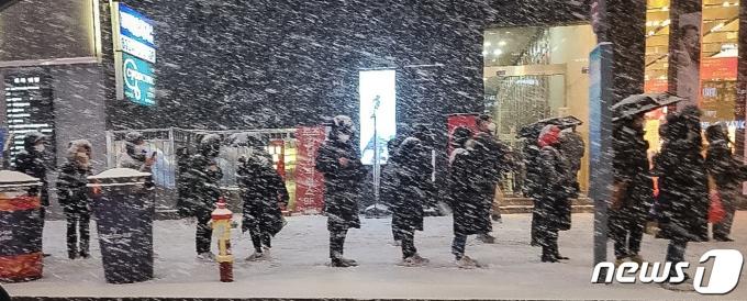 북극발 찬공기 영향으로 중부지역과 내륙을 중심으로 한파가 이어지고 있는 지난 6일 저녁 서울 강남역 인근에서 시민들이 눈발을 맞으며 버스를 기다리고 있다.  2021.1.6/뉴스1 © News1 이동원 기자