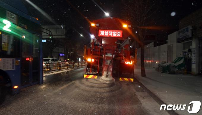 전국 곳곳에 대설 특보가 발효중인 17일 저녁 눈이 내린 서울 동작구 장승배기역 인근 상도로에서 제설 차량이 도로에 염화칼슘을 뿌리며 이동하고 있다. (동작구청 제공) 2021.1.17/뉴스1