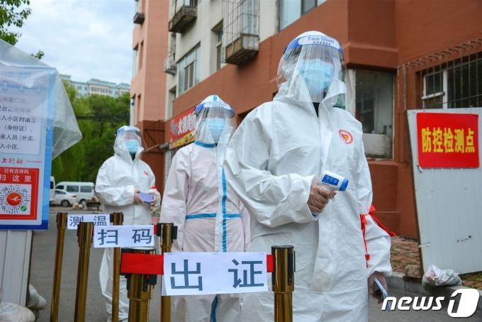 지난해 5월25일 중국 지린성의 주거지에 설치된 검문소에서 보호복을 입은 자원봉사자들이 서 있다. © AFP=뉴스1