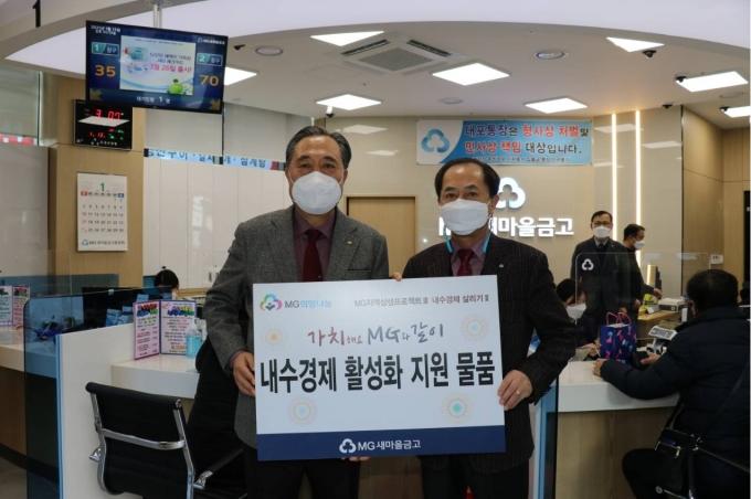 박차훈(왼쪽) 새마을금고중앙회장이 권기찬 반송새마을금고 이사장에 내수경제 활성화 지원사업을 위한 물품을 전달하고 있다./사진=새마을금고중앙회