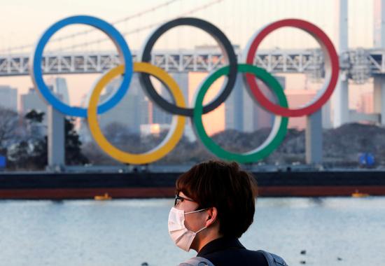 일본이 코로나19으로 인해 도쿄올림픽을 한 차례 연기한 데 이어 올림픽 재연기에 대한 논의를 진행 중인 것으로 알려졌다. 사진은 지난 13일(현지시각) 일본 도쿄의 올림픽 링 앞에 서 있는 한 시민의 모습. /사진=뉴스1(로이터)