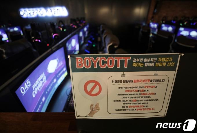 정부의 거리두기 2.5단계 연장안이 발표된 18일 서울의 한 PC방에서 관계자가 영업을 종료 해야만 하는 저녁 9시가 되자 불은 켜두고 영업은 하지 않는 '점등시위'를 하고 있다. 한국인터넷콘텐츠서비스협동조합 소속 PC방 업주들은 이날부터 영업제한에 항의하는 의미로 오후 9시 이후 점등시위를 이어나갈 예정이다. 2021.1.18/뉴스1 © News1 이성철 기자