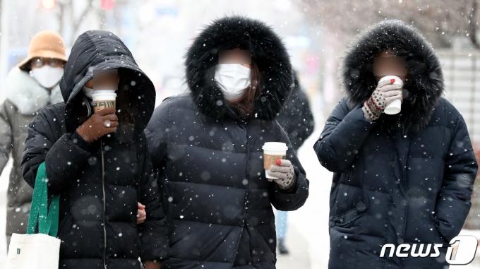 대전지역에 많은 눈이 내린 18일 오후 대전 서구에서 시민들이 커피를 마시며 이동하고 있다. 2021.1.18/뉴스1 © News1 김기태 기자