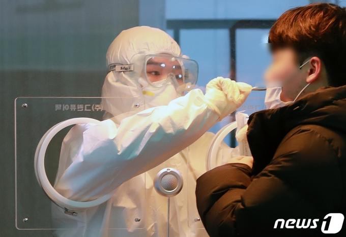 18일 오전 서울역 앞 광장에 마련된 코로나19 임시선별진료소에서 의료진이 검체를 채취하고 있다. /뉴스1 © News1 구윤성 기자
