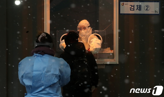 18일 오후 서울역 앞 광장에 마련된 코로나19 임시선별진료소에서 의료진이 검체를 채취하고 있다. /뉴스1 © News1 김진환 기자