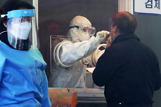19일 서울역광장에 마련된 임시선별검사소에서 의료진이 시민을 대상으로 코로나19 진단검사를 하고 있다. /사진=뉴스1