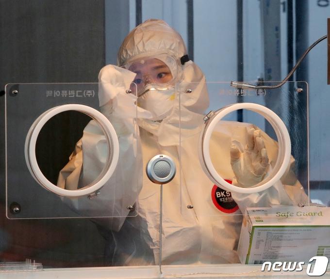 18일 오후 서울역 앞 광장에 마련된 코로나19 임시선별진료소에서 의료진이 검사대를 깨끗하게 닦고 있다. /뉴스1 © News1 김진환 기자