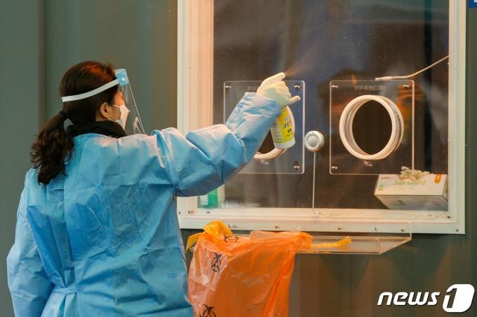 21일 오전 서울역 광장에 마련된 중구 임시선별검사소에서 관계자가 검체채취실을 소독하고 있다. 2021.1.21/뉴스1 © News1 안은나 기자