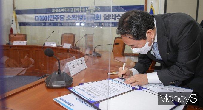 [머니S포토] 협약서에 서명하는 김태현 금융위원회 사무처장