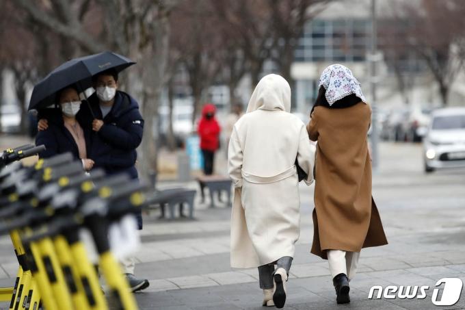 22일 오전 광주 북구 전남대학교에서 우산을 쓴 시민과 손수건으로 머리를 가린 시민들이 길을 걷고 있다. 이날 광주는 영상의 날씨를 보인 가운데 겨울비가 내렸다.(광주북구 제공)2021.1.22/뉴스1 © News1 허단비 기자