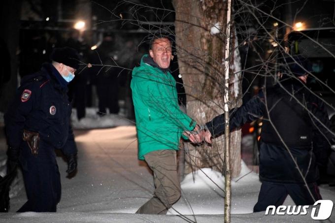 러시아 야권 운동가 알렉세이 나발니가 18일(현지시간) 독극물 중독 치료 뒤 독일서 귀국 직후 체포돼 법원의 30일간 구속 판결을 받고 모스크바 외곽 힘키 경찰서에서 호송되고 있다. © AFP=뉴스1
