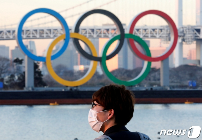 일본 도쿄의 올림픽 상징물 앞으로 한 행인이 마스크를 쓴 채 지나가고 있다. © 로이터=뉴스1