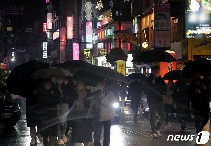 21일 서울 시내의 유흥주점 밀집지역에서 저녁 9시가 되자 거리로 쏟아지는 시민들과 가게 문을 닫은 채 간판 불을 켜는 '점등 시위'가 이어지고 있다. 2021.1.21/뉴스1 © News1 이동해 기자