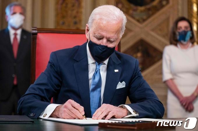 조 바이든 미국 대통령이 워싱턴 백악관에서 취임 후 첫 업무로 파리 기후변화 협약 복귀 등 3건의 행정명령에 서명을 하고 있다. © AFP=뉴스1 © News1 우동명 기자