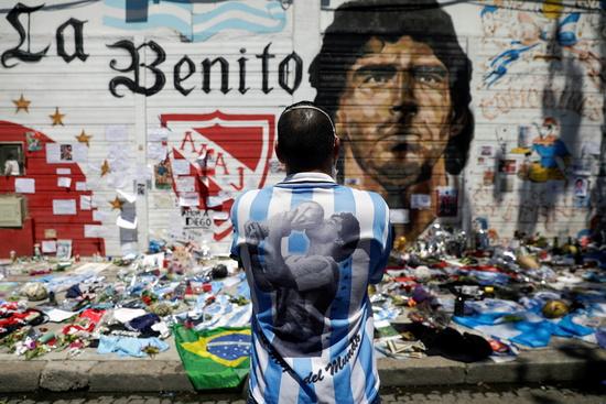 지난해 11월 아르헨티나 부에노스 아이레스의 한 길거리에서 축구팬이 디에고 마라도나의 얼굴이 새겨진 벽화 앞에 서서 마라도나를 추모하고 있다. /사진=로이터