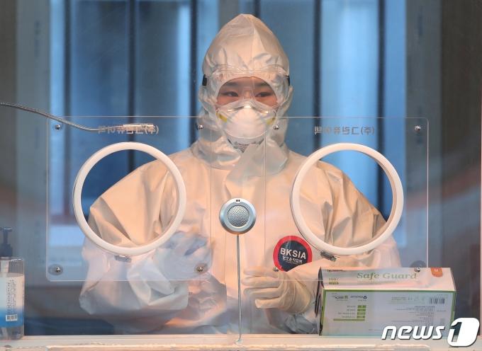 17일 오전 서울역 광장에 마련된 신종 코로나바이러스 감염증(코로나19) 임시선별진료소에서 한 의료진이 영하의 날씨에 핫팩으로 추위를 녹이고 있다. 질병관리청 중앙방역대책본부는 이날 0시 기준 코로나19 신규 확진자가 520명 발생했다고 밝혔다. 2021.1.17/뉴스1 © News1 임세영 기자