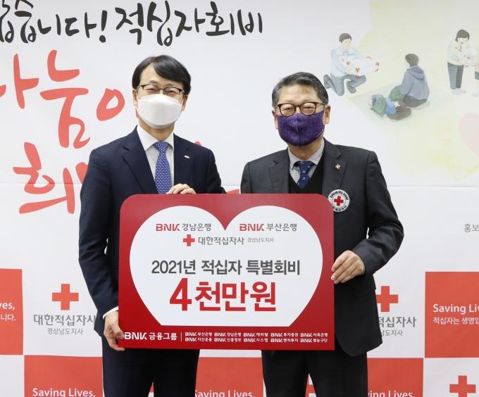 BNK경남은행 고영준 상무(왼쪽)가 김종길 대한적십자사 경남지사 회장에게 '2021년 대한적십자 특별회비 납부 증서'를 전달하고 있다./사진=BNK경남은행