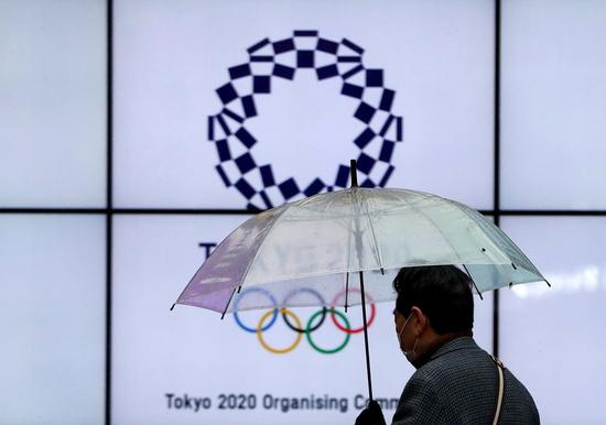 일본 도쿄에서 한 시민이 마스크를 쓰고 우산을 든 채 도쿄올림픽 홍보물 앞을 지나고 있다. /사진=로이터