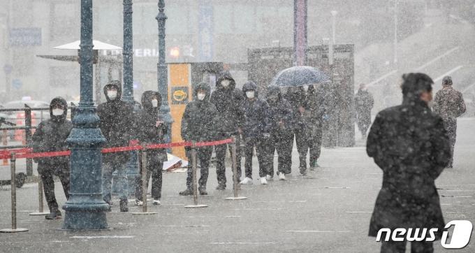 대설주의보가 발효된 28일 서울역광장에 마련된 신종 코로나바이러스 감염증(코로나19) 중구임시선별검사소를 찾은 시민들이 눈을 맞으며 코로나19 검체채취를 기다리고 있다.  © News1 유승관 기자