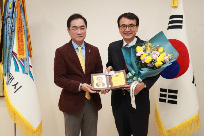 경기 평택시는 지난 28일 시장 집무실에서 김인국 평택 SOFA국민지원센터장에게 명예시민패를 수여했다.(왼쪽부터 정장선 시장, 김인국 센터장). / 사진제공=평택시