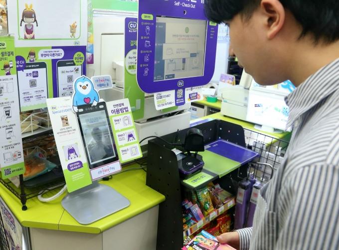 신한카드 고객이 CU한양대생활관점에서 필요한 물품을 고른 후 신한 페이스페이로 결제를 진행하고 있다./사진=신한카드