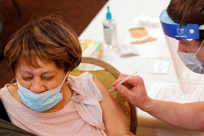 신종 코로나바이러스 감염증(코로나19) 백신 우선접종 대상을 둘러싼 논란이 일고 있다. 사진은 미국 뉴욕주에 위치한 예방접종 센터에서 한 여성이 코로나19 백신을 접종받고 있는 모습. /사진=로이터
