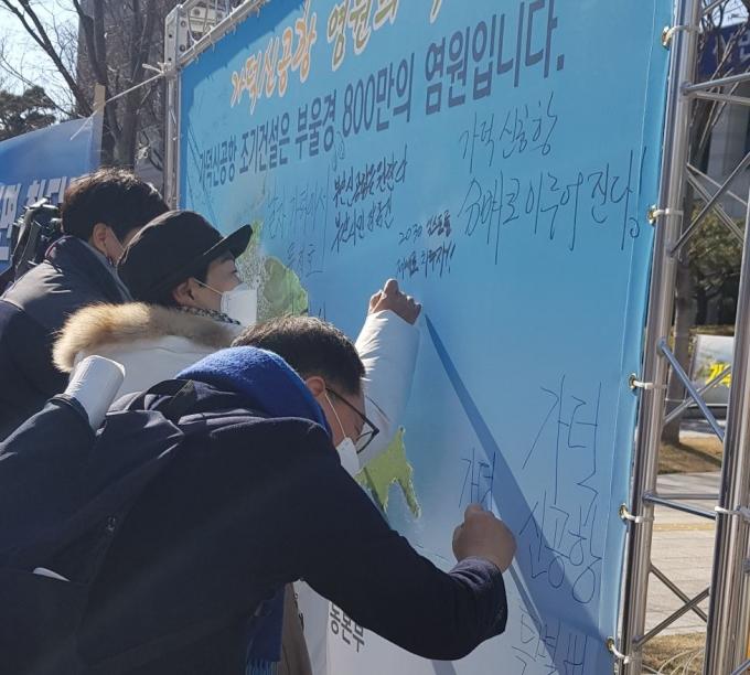 지난 18일 진행된 가덕신공항특별법 통과 기원 '염원의 벽'에 메시지를 남기는 부산시민들./사진=가덕도신공항유치국민행동본부