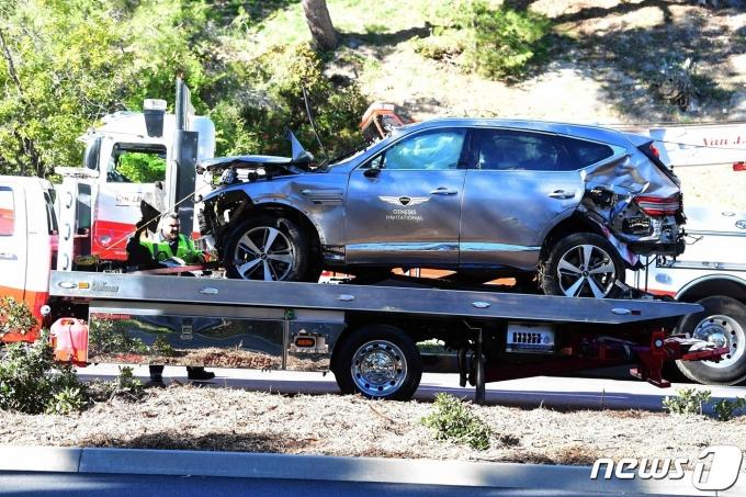 '골프 황제' 타이거 우즈가 탄 차량이 23일(현지시간) 캘리포니아주 로스앤젤레스의 란초 팔로스 베르데스 인근에서 전복된 뒤 옮겨지고 있다. 우즈는 병원으로 긴급 이송돼 다리 수술을 받은 것으로 알려졌다. © AFP=뉴스1