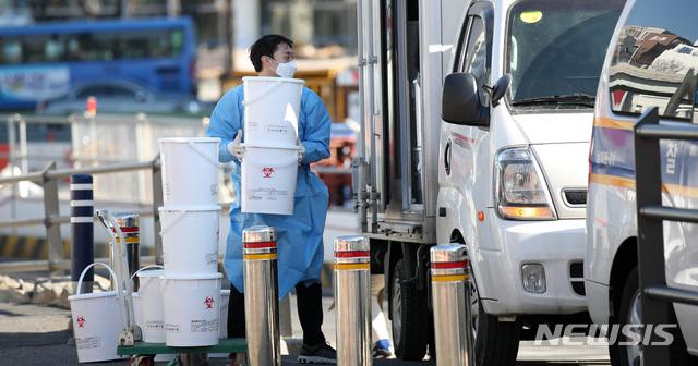 지난 9일 서울역 광장에 설치된 중구 임시 선별검사소에서 한 관계자가 의료폐기물을 처리하고 있다./사진=뉴시스