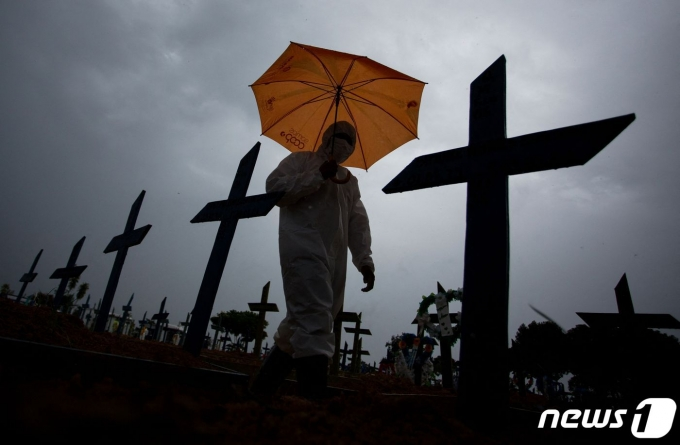 2월25일 코로나19 희생자들이 묻혀 있는 브라질의 한 묘지를 방호복을 입은 한 남성이 걸어가고 있다.  © AFP=뉴스1