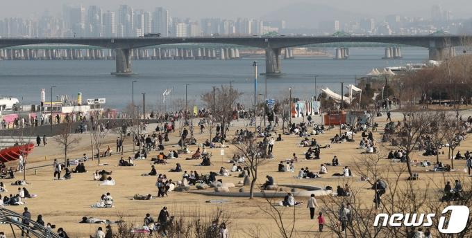 완연한 봄날씨를 보인 21일 오후 서울 여의도 한강공원을 찾은 시민들이 모처럼 따뜻한 봄기운을 만끽하고 있다. 2021.2.21/뉴스1 © News1 박지혜 기자