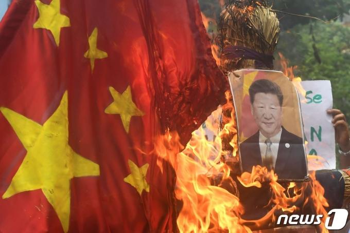인도 시민들이 시진핑 중국 국가주석의 사진을 불태우는 모습.© AFP=뉴스1