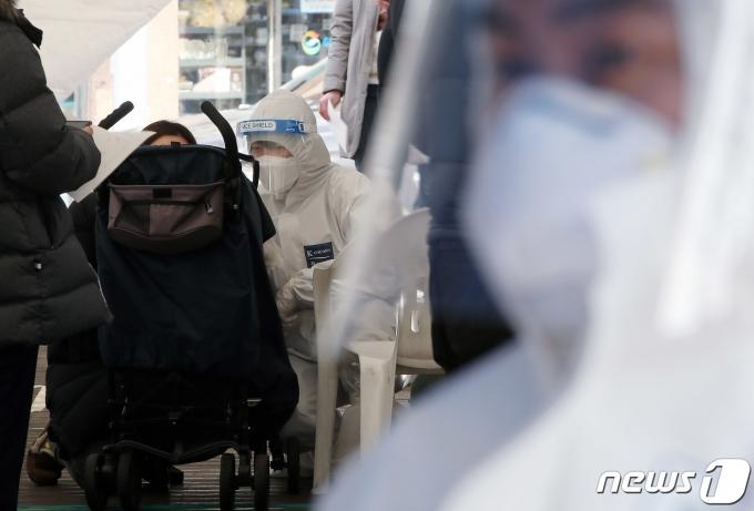 서울 성북구청 바람마당에 설치된 임시선별진료소에서 엄마와 함께 온 아이가 유모차에 앉아 신종 코로나 바이러스 감염증(코로나19) 검사를 받고 있다. 2021.2.5/뉴스1 © News1 박정호 기자