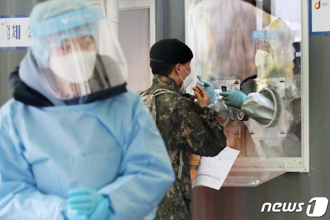 지난 24일 오전 서울역 광장의 코로나19 임시선별검사소에서 군 장병(가운데)이 진단검사를 받고 있다. 2021.2.24/뉴스1 © News1 민경석 기자
